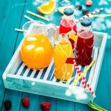 Butelki świeżo gniosący pomarańczowy i jagodowy sok Zdjęcia Royalty Free