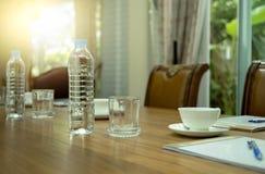 Butelki woda i filiżanka kawy na drewnianym stole w konferenci Fotografia Royalty Free