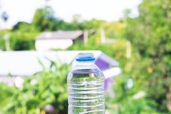 Butelki woda zrobił klingeryt na drewnianym i drzewnym rozmytym bokeh tle w ogródzie Używać tapetę dla pakunku lub produktu i Zdjęcie Stock