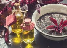 Butelki z amarantu olejem, roślinami i amarantów ziarnami, Zdjęcie Stock