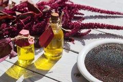 Butelki z amarantu olejem, roślinami i amarantów ziarnami, Fotografia Stock