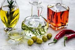 Butelki z banią, chili, oliwa z oliwek i ziele na kamiennym tle, Obraz Stock