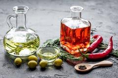 Butelki z chili, oliwa z oliwek i ziele na kamiennym tle Fotografia Stock