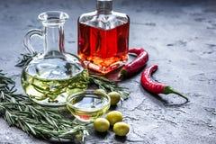 Butelki z chili, oliwa z oliwek i ziele na kamiennym tle Zdjęcie Stock