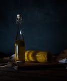 Butelki z olejem, ziele i pikantność przy drewnianym stołem na czarnym tle, Fotografia Stock