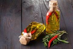Butelki z olejem, ziele i pikantność przy drewnianym stołem na czerń plecy, Obraz Royalty Free