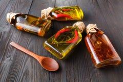 Butelki z olejem, ziele i pikantność przy drewnianym stołem na czerń plecy, Obrazy Royalty Free