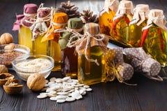Butelki z olejem, ziele i pikantność przy drewnianym stołem na czerń plecy, Fotografia Stock