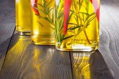 Butelki z olejem, ziele i pikantność przy drewnianym stołem na czerń plecy, Obrazy Stock