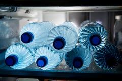 Butelki zimna odświeżająca woda mineralna w chłodziarce Zdjęcia Royalty Free