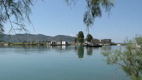 Simple car ferry crossing the Vivari Channel in Buthrotum, also known as Butrint Albania next to the ruin city of roman and vene stock video