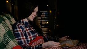 Butiful kobieta czyta książkę i trzepnięcia przez stron pod koc na leżance zbiory wideo