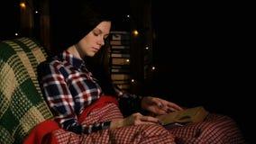 Butiful kobieta czyta książkę i trzepnięcia przez stron pod koc na leżance zdjęcie wideo