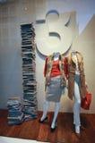 Butikenshopfenster mit gekleideten Mannequins und hohem Stapel von BO Stockfoto