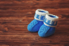 Butins bleus de bébé de crochet sur le fond en bois, copyspace, vintage modifié la tonalité Images stock