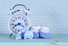 Butins bleus et blancs de crèche de bébé garçon et horloge Photos libres de droits