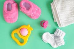 Butins de vêtements et de bébé du ` s d'enfants sur le fond vert Photo libre de droits
