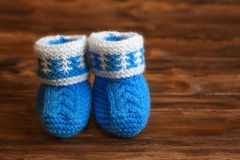 Butins fabriqués à la main bleus de bébé de crochet sur le fond en bois, copyspace Image libre de droits