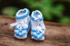 Butins fabriqués à la main bleus de bébé de crochet sur le fond en bois, plan rapproché Photos libres de droits