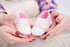 Butins roses pour le bébé nouveau-né dans des mains de maman et de papa Grossesse Photos libres de droits