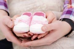 Butins roses pour le bébé nouveau-né dans des mains de maman et de papa Grossesse Images stock