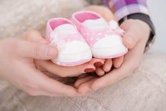 Butins roses pour le bébé nouveau-né dans des mains de maman et de papa Grossesse Photo stock
