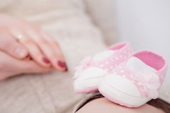 Butins roses pour le bébé nouveau-né dans des mains de maman et de papa Grossesse Photographie stock