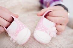 Butins roses pour le bébé nouveau-né dans des mains de papa Grossesse Images stock