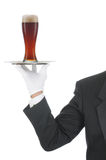 Butler with beer on Tray. Butler wearing tuxedo and formal gloves holding a beer glass on a silver tray. Shoulder hand and arm only isolated on white vertical Royalty Free Stock Image