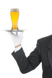 Butler with Beer on Tray. Butler wearing tuxedo and formal gloves holding a beer glass on a silver tray. Shoulder hand and arm only isolated on white vertical Stock Image