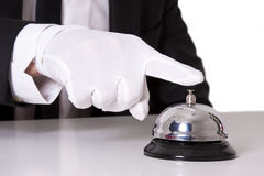Butler bell. Gloved hand on the bell of the hotel Stock Images