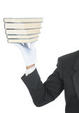 Butler with Books. Butler wearing tuxedo and formal gloves holding up a stack of books. Shoulder hand and arm only isolated on white vertical composition stock photo