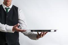 Butler/camarero en el chaleco del traje que lleva una bandeja de plata vacía imagen de archivo libre de regalías