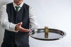 Butler/cameriere tiene un vassoio d'argento con una banconota in dollari dieci fotografie stock libere da diritti