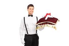 Butler che tiene un cuscino rosso con due diplomi dell'università Immagine Stock