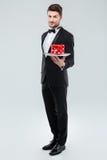 Butler dans le smoking tenant et tenant le plateau avec le boîte-cadeau photographie stock libre de droits