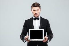 Butler dans le smoking tenant le comprimé d'écran vide sur le plateau photo stock