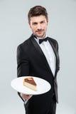 Butler dans le smoking tenant le morceau de gâteau de plat image stock