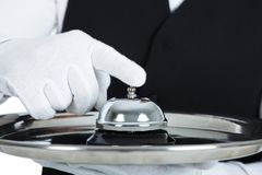 Butler, das Service-Glocke hält Lizenzfreies Stockfoto