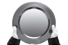 Butler, der ein silbernes Tellersegment anhält Stockfotografie