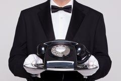Butler, der ein Telefon auf Silbertablett anhält Lizenzfreies Stockbild