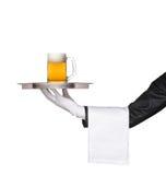 Butler, der ein Tellersegment mit einem Bierglas auf ihm anhält Lizenzfreies Stockfoto