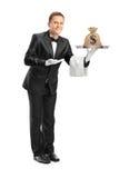 Butler die een dienblad met een geldzak houdt op het stock foto