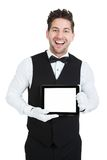 Butler displaying digital tablet. Portrait of young butler displaying digital tablet over white background royalty free stock photo