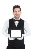 Butler displaying digital tablet. Portrait of young butler displaying digital tablet over white background royalty free stock image