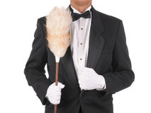 Butler with Duster. Butler in a tuxedo Holding a duster isolated on white torso only stock image