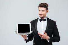 Butler en el smoking que se sostiene y que señala en la tableta de la pantalla en blanco Imagenes de archivo