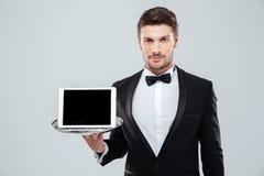 Butler en el smoking que sostiene la tableta de la pantalla en blanco en la bandeja Fotografía de archivo