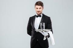 Butler en los guantes que sostienen el vidrio de agua en la bandeja de plata Foto de archivo libre de regalías