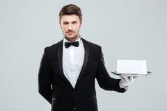 Butler en smoking y guantes que sostienen la bandeja con la tarjeta en blanco fotografía de archivo
